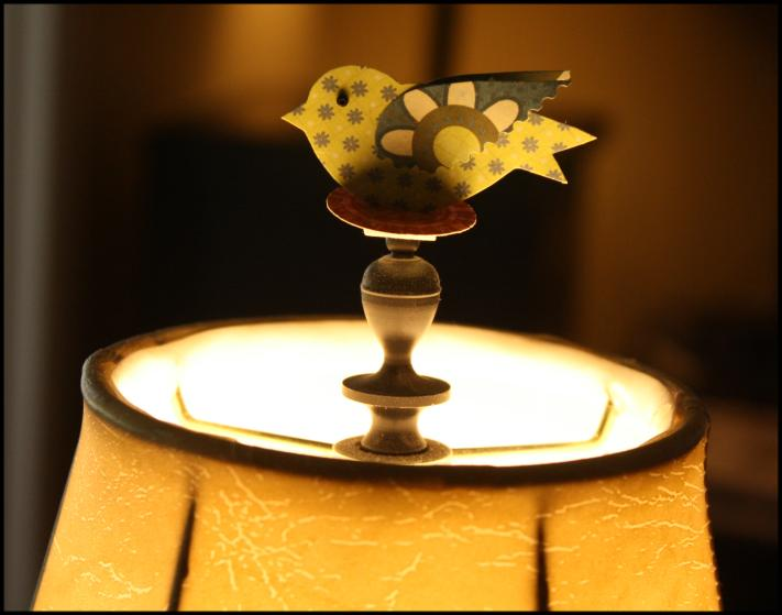 Paper birdie on lamp finial