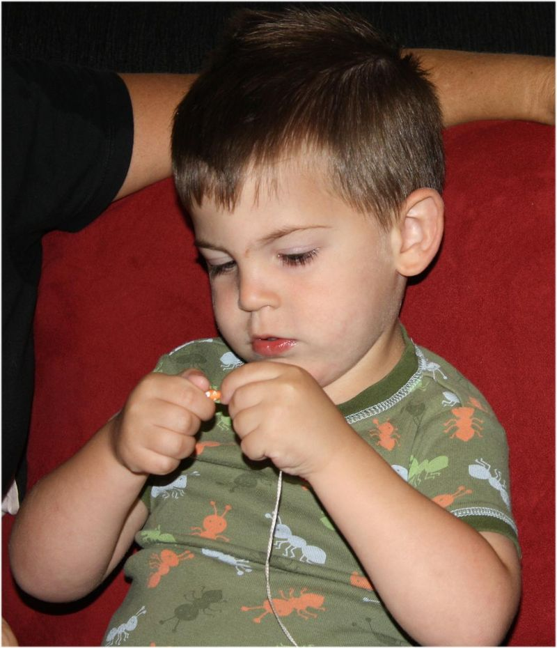 Little Man stringing paper beads.